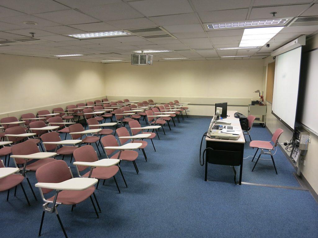 Sivukuva tyhjästä luokasta, jossa oikealla opettajan pöytä ja vasemmalla neljässä rivissä tuoleja
