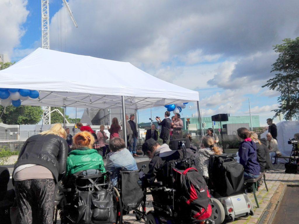Pyörätuolissa istuvia henkilöitä telttakatoksen edessä, jonka päädyissä on sinisiä ja valkoisia ilmapalloja.